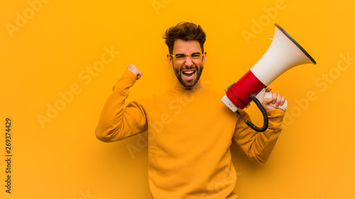 Fotografía  Young man holding a megaphone surprised and shocked