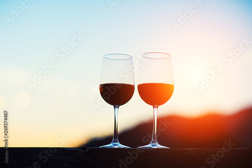 Papiers peints Alcool Two glasses of wine at sunset dramatic sky on mountain landscape background