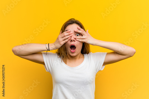 Fotografía  Young natural caucasian woman blink through fingers frightened and nervous