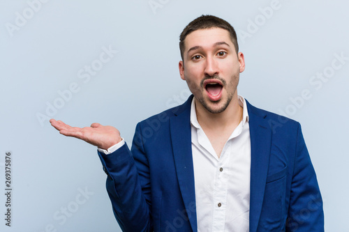 Obraz na plátne  Young business caucasian man impressed holding copy space on palm