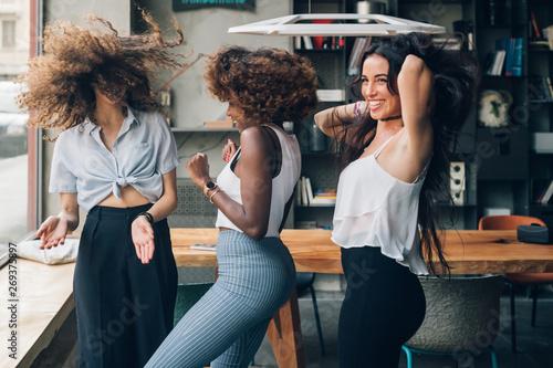 Foto  three multiracial women dancing in modern loft