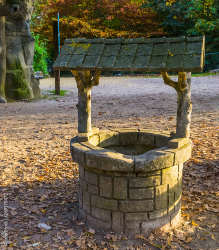 Photo Stands Fantasy Landscape classical water well, medieval looking architecture, historical decorations