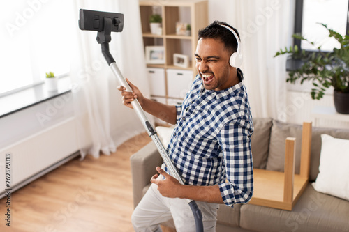 Valokuva  household and cleaning concept - indian man in headphones with vacuum cleaner ha