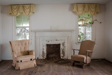 Living Room With Two Chairs With A Fireplace In An Abandoned Home