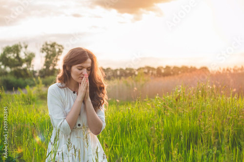 Stampa su Tela Girl closed her eyes, praying in a field during beautiful sunset