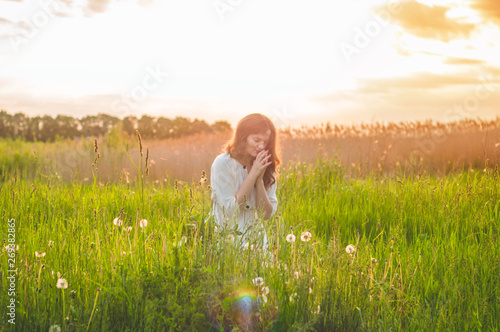 Fotomural Girl closed her eyes, praying in a field during beautiful sunset