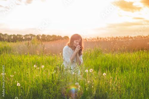 Valokuvatapetti Girl closed her eyes, praying in a field during beautiful sunset
