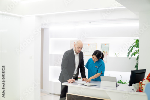 Fototapety, obrazy: Young Assistant make Appointment on Reception in Dental Clinic