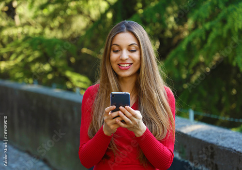 Beautiful young woman using smart phone in the park Canvas Print