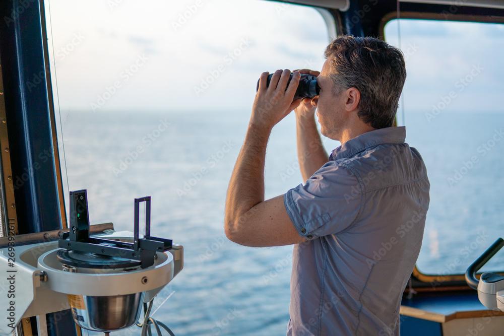 Fototapety, obrazy: Navigational officer lookout on navigation watch looking through binoculars. Marine industry. COLREG collision regulations