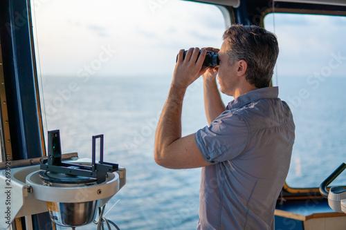 Navigational officer lookout on navigation watch looking through binoculars Fototapet