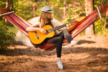 Woman In Hat Play Guitar And Relaxing In Hammock Hanging Among Pine Trees In Background. Camping Rest Concept