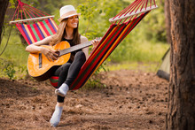 Woman In Hat Play Guitar And Relaxing In Hammock In Middle Of Forest. Slow Life Concept. Hipster.