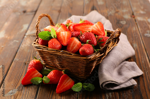 strawberry and mint in basket on wood background