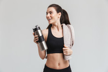 Beautiful Young Sport Fitness Woman Drinking Water Isolated Over Grey Wall Background.