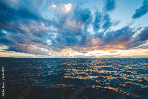 Foto auf Leinwand Blau Jeans Sunset sea view with dramatic sky and colorful clouds
