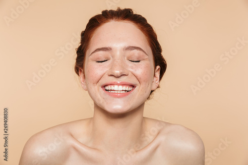 Obraz Amazing young redhead woman posing isolated over beige wall background. - fototapety do salonu