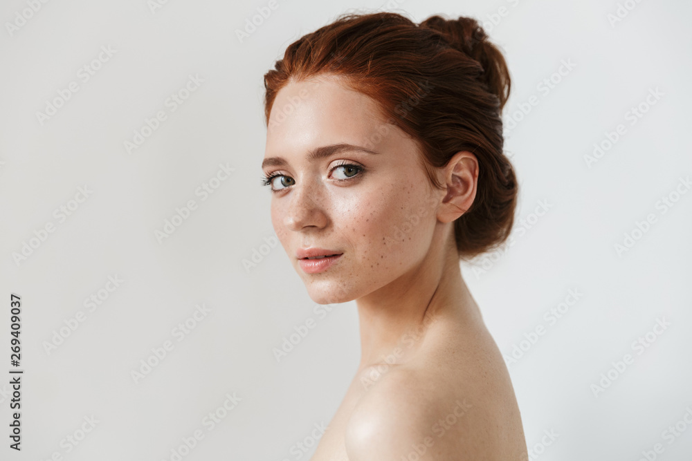 Fototapeta Young redhead woman posing isolated over white wall background.