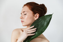 Young Redhead Woman Posing Isolated Over White Wall Background With Leaf Green Flowers.
