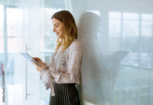 Attractive businesswoman using a digital tablet while standing in the office