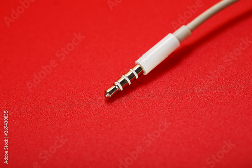 White connector AUX white cable on a red background Wallpaper Mural