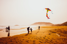 Silhouettes Of People Playing And Flying A Kite In Sandy Golden Beach, Karpasia, Cyprus
