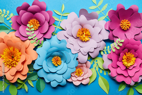 Fotografía  top view of bright colorful paper cut flowers with green leaves on blue backgrou