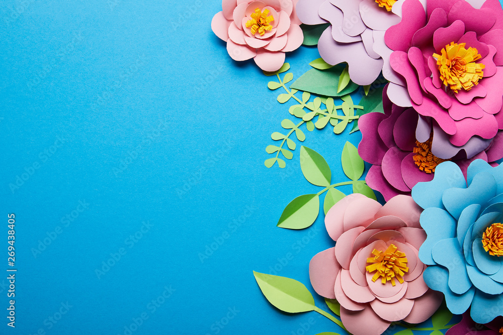 Fototapeta top view of colorful paper cut flowers with green leaves on blue background with copy space