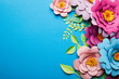 Leinwandbild Motiv top view of colorful paper cut flowers with green leaves on blue background with copy space