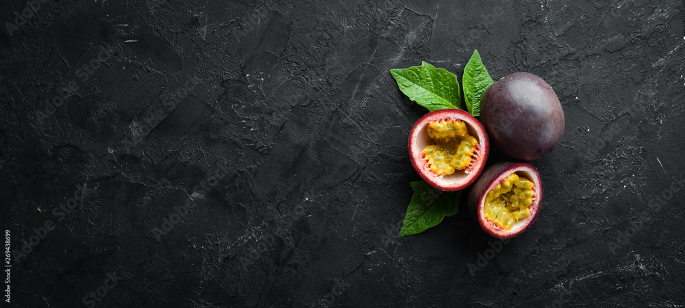 Fototapeta Passion fruits with leaves on a black background. Tropical Fruits. Top view. Free space for text.