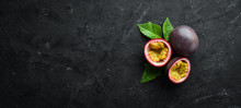 Passion Fruits With Leaves On A Black Background. Tropical Fruits. Top View. Free Space For Text.