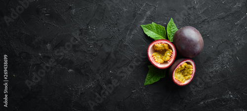 Passion fruits with leaves on a black background. Tropical Fruits. Top view. Free space for text. - 269438699
