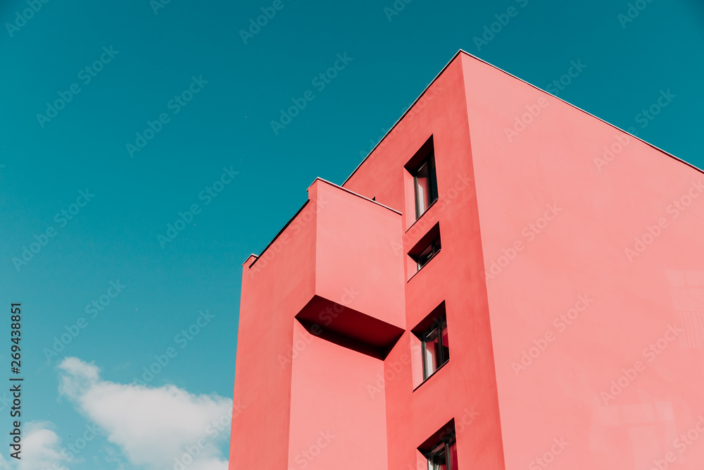 Fototapeta View from below on a pink modern house and sky. Vintage pastel colors, minimalist concept.