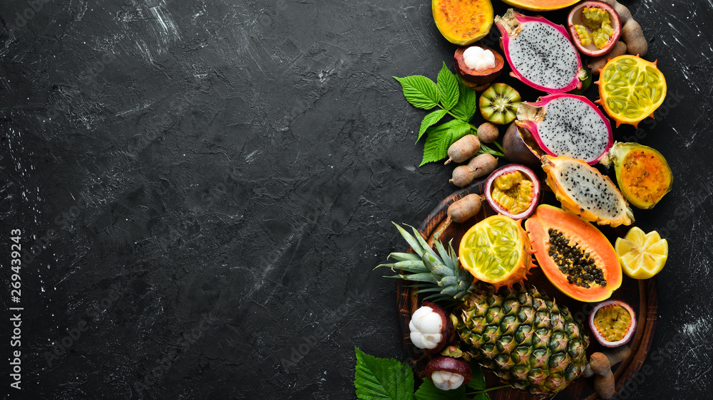 Fototapety, obrazy: Tropical fruits: papaya, mangosteen, cactus fruit, pytahaya, pineapple on a black background. Top view. Free space for text.