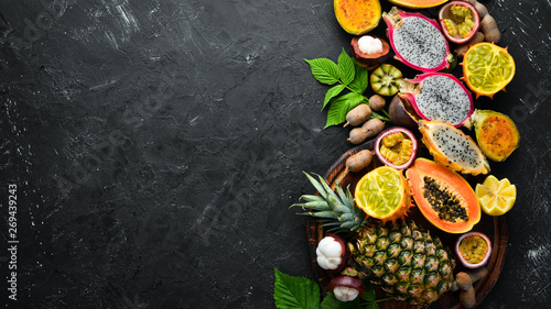 Tropical fruits: papaya, mangosteen, cactus fruit, pytahaya, pineapple on a black background. Top view. Free space for text.