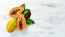 Sweet Ripe Fresh Papaya On A White Wooden Background. Top View. Free Space For Text.