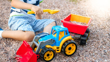 Portrait Of Adorable 3 Years Old Toddler Boy Playing With Toy Truck With Trailer On The Playground At Park. Child Digging And Building From Sand