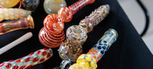 Glass Smoking Pipes On A Black Background. Design Accessories For Smoking Marijuana.