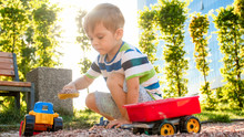 Photo Of Adorable 3 Years Old Toddler Boy Playing With Sand And You Truck And Trailer In Park. Child Digging And Building In Sandpit