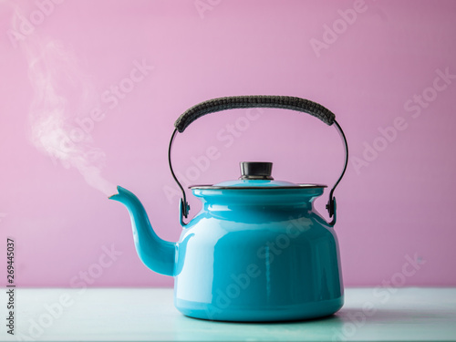 Fényképezés  Steaming kettle with boiling water against pink background