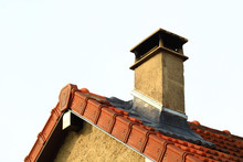 Classic Fireplace Exit With Sebicape Hat On Roof Of A House.  Roof With Aligned Edge And Ridge Tiles And Red Pediment