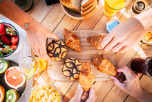 Vertical View Of Wooden Table And People Together For Breakfast In Friendship - Brioches And Cakes And Fruit To Start The Day - Happy Lifestyle Concept With Hands Taking Delicious