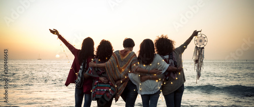 Romance and emotion concept with group of people women friends viewed from back hugging and ejoying the sunset in outdoor nature sea vacation concept - friendship and freedom for travelers