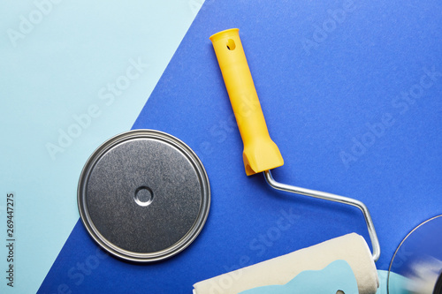 top view of metal cap near roller on bright blue background