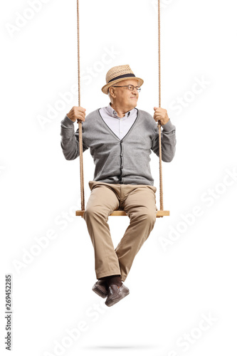 Fototapety, obrazy: Senior man sitting on a swing and looking away