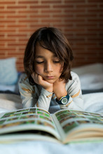 Kid Reading A Book Laying On Bed