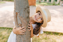 Funny Dark-haired Kid With Big Eyes And Smile Embracing Tree In Park. Outdoor Portrait Of Happy Little Girl In Straw Hat Enjoying Summer Vacation.