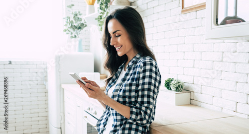 Foto  Beautiful cute smiling woman is using smart phone on the kitchen at home