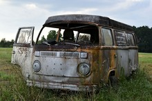 A Classic Bus Sits Abandoned In The Middle Of A Grassy, Southern Field.