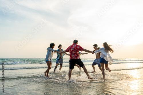 Fototapeta A group of male and female friends who play fun on the sea beach amid the sunset. obraz na płótnie